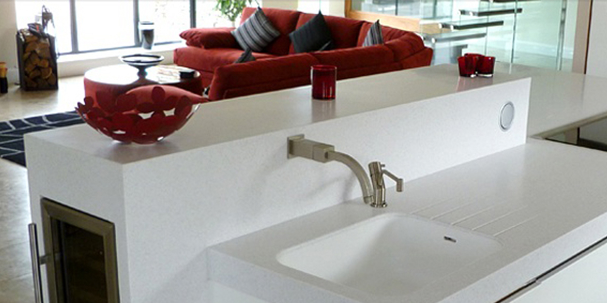 Bespoke Corian Kitchen Island With Integrated Hob And Feature Trough Sink.